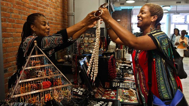 Rashida Watson (left) gives Jasmine Burnett, Deputy Director of New Voices for Reproductive Justice, a shell necklace to try on. (Kimberly Paynter/WHYY)
