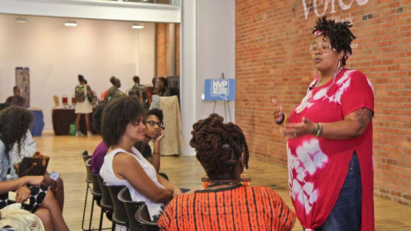 Jewelry maker Sheba Gibbons gives a talk about natural hair products at the Kinks, Locks and Twists Conference Thursday afternoon. (Kimberly Paynter/WHYY)