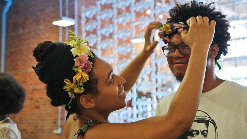 Helanah Warren crowns Kyree Frazier with flowers at the Kinks, Locks and Twists Conference Thursday afternoon. (Kimberly Paynter/WHYY)
