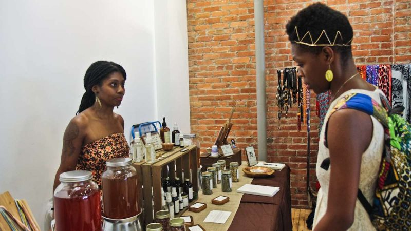 Quaver Johnson (left) and Arin Maya talk about natural products at the Kinks, Locks and Twists Conference. (Kimberly Paynter/WHYY)