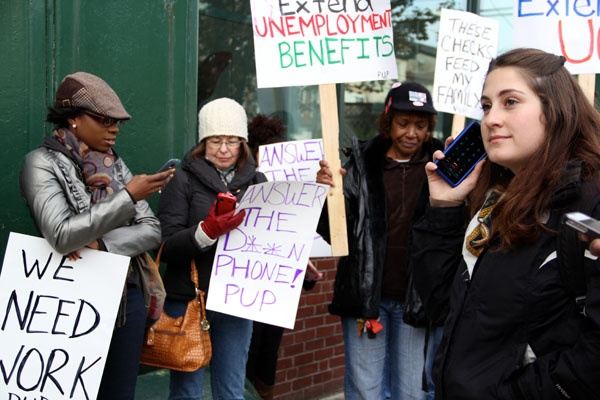 <p>During a rally on Spring Garden Street, protestors dial the unemployment hotline. Most got a busy signal. (Emma Lee/for NewsWorks)</p>