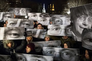 Mourners at Union Square in New York City hold signs depicting victims' eyes during a rally in support of 'Charlie Hebdo,' a French satirical newspaper that fell victim to a terrorist attack on Wednesday, Jan. 7, 2015. (AP Photo/John Minchillo)