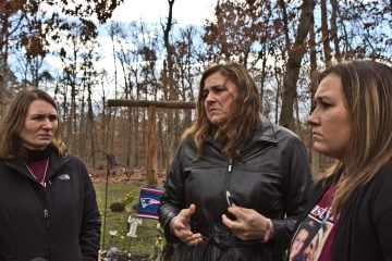 Tiffany's sister Jessie Vallauri, mother Dianne Valiante, and sister Krystal Summerville, stand near a memorial to her in the yard of the family's home. (Kimberly Paynter/WHYY)