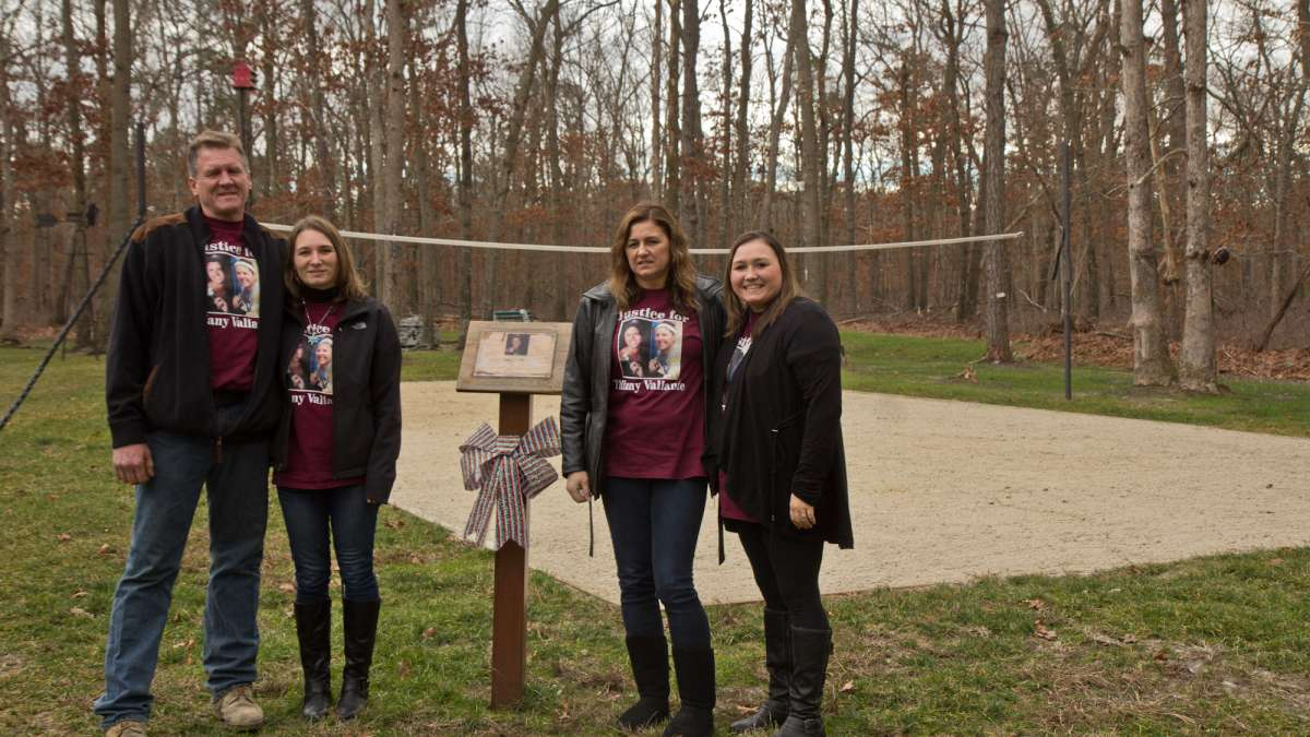 Tiffany's father Stephen Valiante, sister Jessie Vallauri, mother Dianne Valiante, and sister Krystal Summerville stand in front of a volleyball court the family installed in the yard in memory of Tiffany.