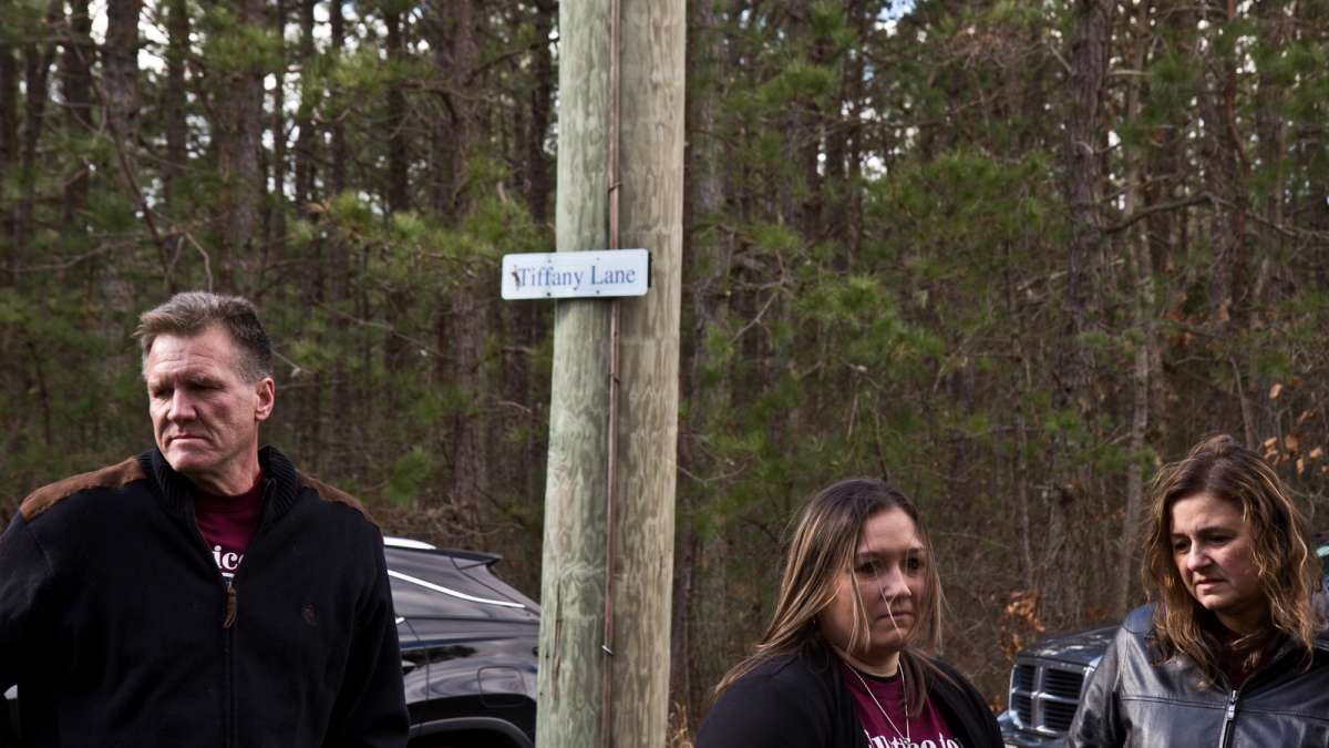 Tiffany's father Stephen Valiante, sister Krystal Summerville, and mother Dianne Valiante stand beneath a sign commemorating Tiffany near the tracks where she was fatally struck.