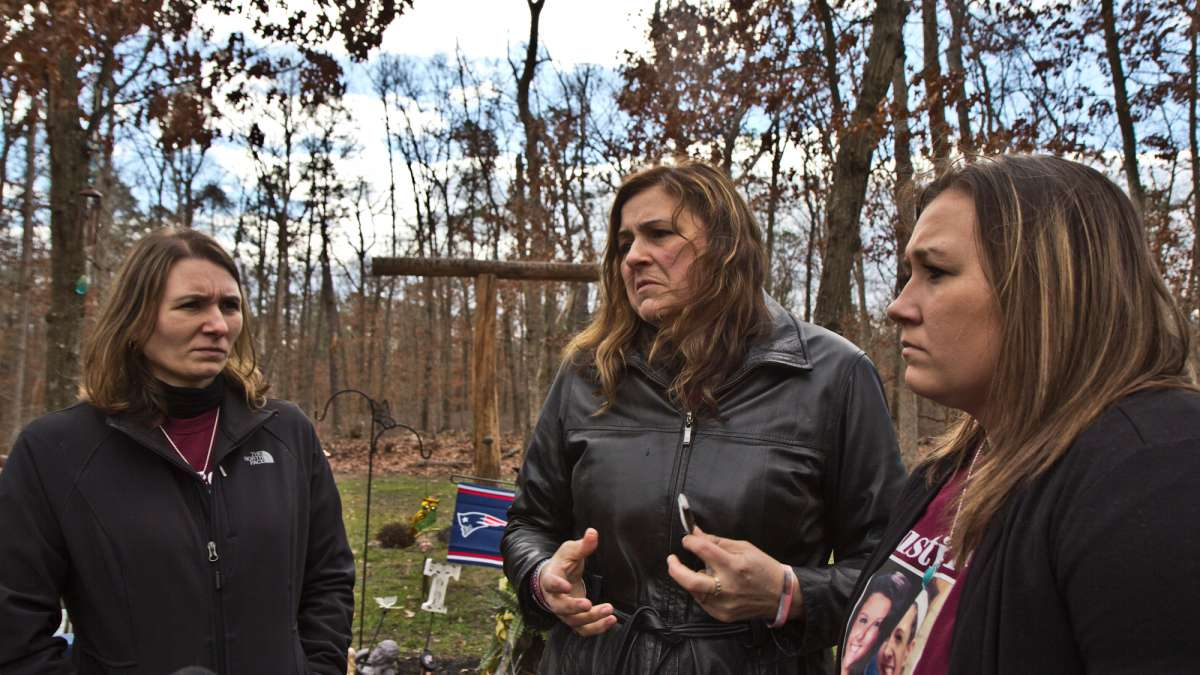 Tiffany's sister Jessie Vallauri, mother Dianne Valiante, and sister Krystal Summerville, stand near a memorial to her in the yard of the family's home.