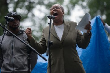 Lois Moses, of West Chester, reads her poetry aloud for the crowd during the People's Poetry and Jazz Festival in Germantown's Vernon Park Saturday afternoon.