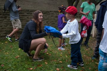 Jayden Hughes, 5, of Allegheny, receives a backpack from volunteer Jessica Hagen, of Mt. Airy, during a back-to-school giveaway at Concord School House Saturday morning in Germantown.