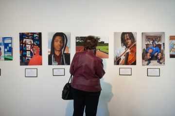 Rose Allen, of Overbrook, looks at photographs by her daughter, Denise Allen, a photographer currently mounting a show at the Mount Airy Arts Garage, during a special reception on Saturday afternoon at the gallery in Mount Airy.