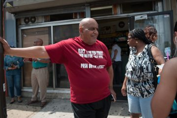 Mayoral candidate T. Milton Street talks with people at the corner of Broad and Erie Tuesday morning.
