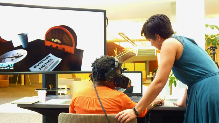 Vanessa Farrell, a program associate at the Robert Wood Johnson Foundation, tries out an empathy-aimed virtual reality experience. Elise Ogle, from Stanford's Virtual Human Interaction Lab, helped design the program. (Todd Bookman/WHYY)