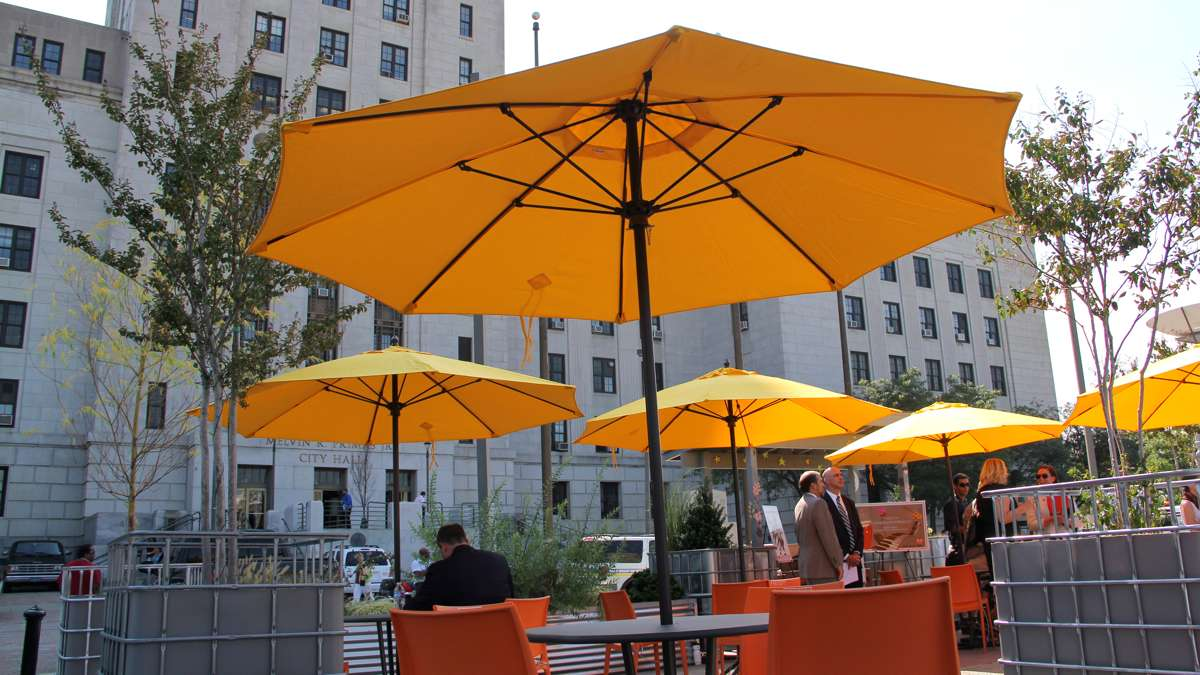 The new park offers plenty of seating under the shade of umbrellas and trees potted in bulk container totes. (Emma Lee/WHYY)