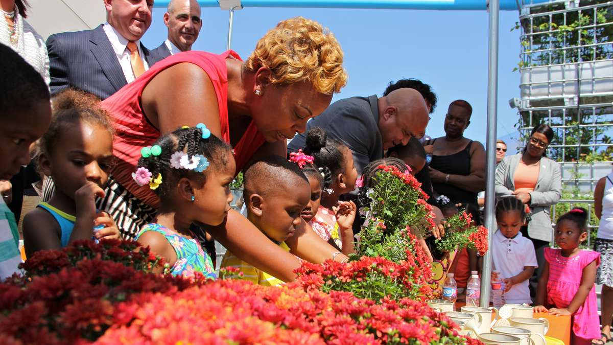 Camden Mayor Dana Redd helps children from Camden Day Nursery repot marigolds at the grand opening of Roosevelt Plaza Park H2O. (Emma Lee/WHYY)