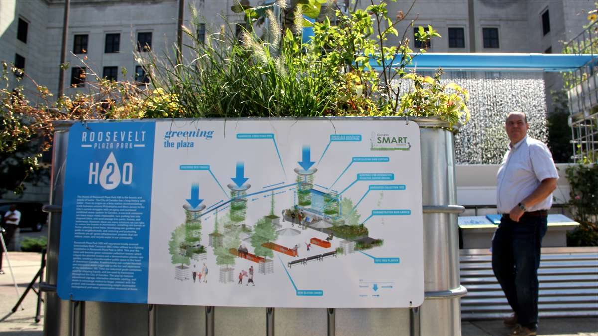 A sign explains the rainwater collection system at Roosevelt Plaza Park and gives visitors pointers on how to conserve water in their own homes. (Emma Lee/WHYY)
