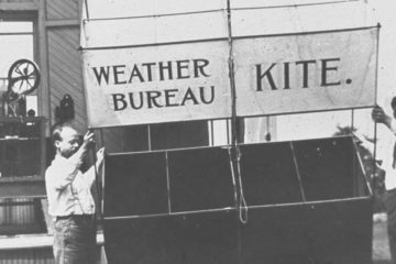 Around 1910, observers prepared to launch this Weather Bureau kite, which would be anchored by the kite-reel house in the background. (Photo via NOAA Photo Library)