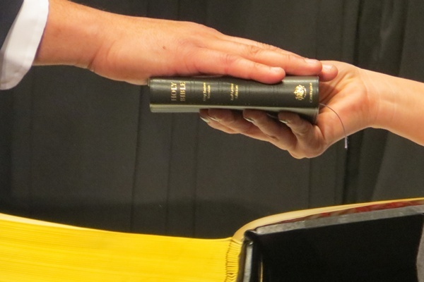 <p><p>Fire chief Anthony Goode's right hand on the bible as he takes his oath of office (Shirley Min/WHYY)</p></p>