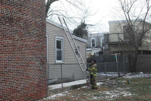 <p>Wilm police and firefighters check roof tops @ 2pm monday on Peach st. for weapons and evidence. (John Jankowski/for NewsWorks)</p>