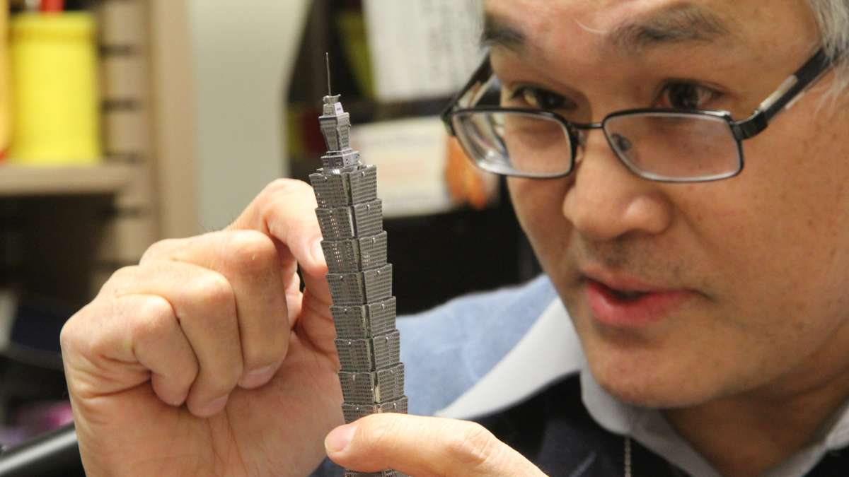 Temple Professor Jim Chen, who specializes in aerodynamics, explains how designers can defeat the wind using a model of Taipei World Financial Center, one of the world's tallest buildings. (Emma Lee/WHYY)