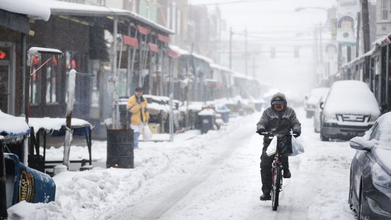 A man rides his bicycle during a winter storm in the Italian Market neighborhood of Philadelphia, Tuesday, March 14, 2017. (AP Photo/Matt Rourke)