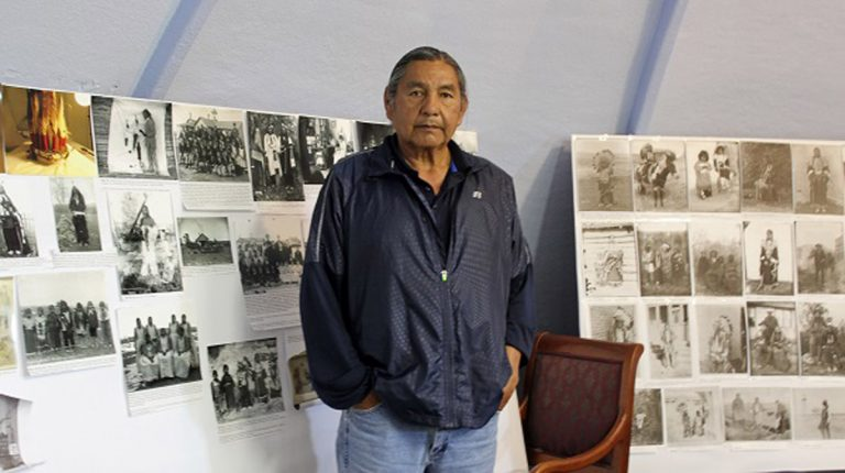 Russell Eagle Bear, the historic preservation officer for the Rosebud Sioux Tribe, looks at photos and maps in his office in Rosebud, S.D., of the Carlisle Indian Industrial School in Pennsylvania. Eagle Bear led a meeting last year between leaders of several tribes, including the Rosebud Sioux Tribe, and representatives from the U.S. Army to address the possibility of repatriating the remains of at least 10 Native American children who died away from their homes while being forced to attend the school more than a century ago. (Regina Garcia Cano/AP Photo)