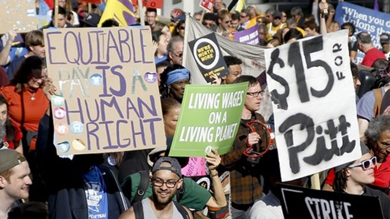 In this April 14, 2016, file photo, union organizers, students, and supporters for a $15 an hour wage march through the Oakland section Pittsburgh. (Keith Srakocic/AP Photo)