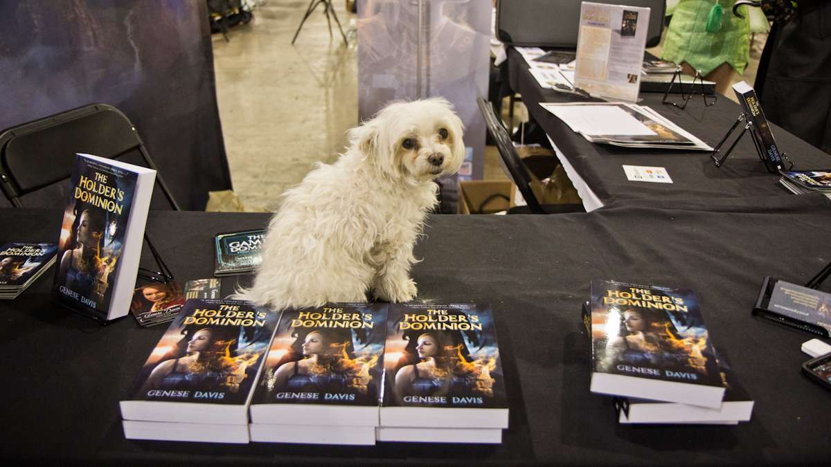 Winston poses on a video game world novel by author Genese Davis.