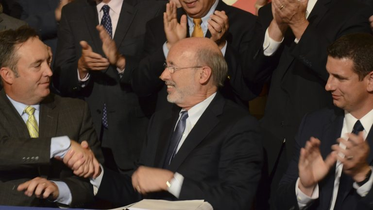Democratic Gov. Tom Wolf shakes hands with Senate Majority Leader Jake Corman, R-Centre, after signing legislation designed to reduce long-term public pension costs during a ceremony in the Pennsylvania Capitol on Monday, June 12, 2017 in Harrisburg, Pa. Looking on at right is House Majority Leader Dave Reed, R-Indiana. (AP Photo/Marc Levy)