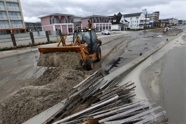 <p>Workers use heavy machinery to clean up damage from superstorm Sandy Tuesday morning, Oct. 29, 2012, in Cape May, N.J., after a storm surge from Sandy pushed the Atlantic Ocean over the beach and across Beach Avenue.  (AP Photo/Mel Evans)</p>