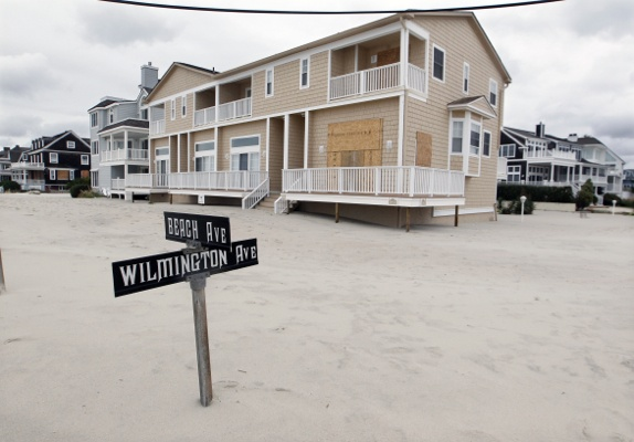 <p>A street sign is partially buried in sand Tuesday morning, Oct. 30, 2012, in Cape May, N.J., after a storm surge from Sandy pushed the Atlantic Ocean over the beach and across Beach Avenue. (AP Photo/Mel Evans)</p>