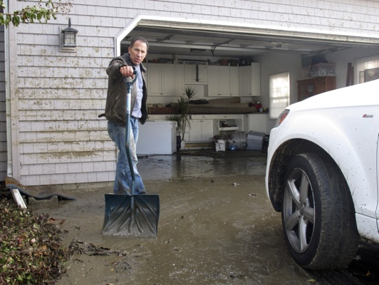 <p>Bill Goldberg shovels mud from the driveway of his home in Point Pleasant Beach, N.J. on Thursday, Nov. 1, 2012. Flooding from Hurricane Sandy inundated his home, and Gioldberg fears he'll have to strip the house down to its wood foundation and rebuild from scratch. (AP Photo/Wayne Parry)</p>