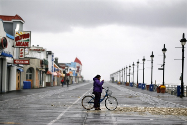 <p>A woman stands alone on the boardwalk Tuesday, Oct. 30, 2012, in Ocean City, N.J., as she photographs sea foam that washed up from the storm surge of Sandy. The storm that made landfall in New Jersey on Monday evening with 80 mph sustained winds killed at least 16 people in seven states, cut power to more than 7.4 million homes and businesses from the Carolinas to Ohio, caused scares at two nuclear power plants and stopped the presidential campaign cold. (AP Photo/Mel Evans)</p>