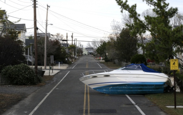 <p>A boat that was carried by surge from Superstorm Sandy sits on a deserted street on Long Beach Island, N.J., Friday, Nov. 2, 2012. Sandy, the storm that made landfall Monday, caused multiple fatalities, halted mass transit and cut power to more than 6 million homes and businesses. (AP Photo/Patrick Semansky)</p>