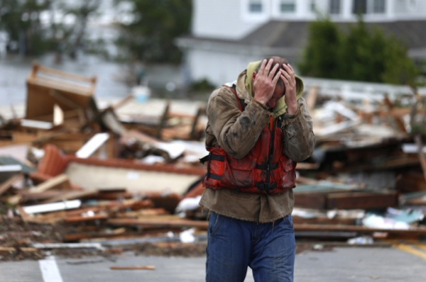 <p>Brian Hajeski, 41, of Brick, N.J., reacts after looking at debris of a home that washed up on to the Mantoloking Bridge the morning after superstorm Sandy rolled through, Tuesday, Oct. 30, 2012, in Mantoloking, N.J. Sandy, the storm that made landfall Monday, caused multiple fatalities, halted mass transit and cut power to more than 6 million homes and businesses. (AP Photo/Julio Cortez)</p>