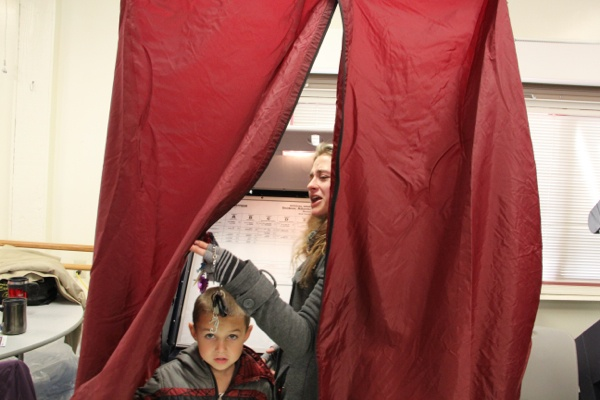 <p><p>First time voter Samantha DeCarlo draws back the curtain of a voting booth in Ventnor to ask her mother for help. (Emma Lee/for NewsWorks)</p></p>
