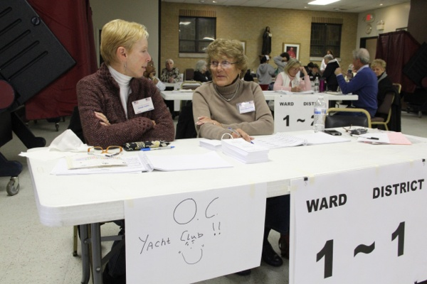 <p>Susan Gailey and Joyce Bakley-Trofa tend the table for voters who usually vote at the Ocean City Yacht Club. The polling place was relocated to St. Francis Cabrini Church, where three other districts vote. (Emma Lee/for NewsWorks)</p>