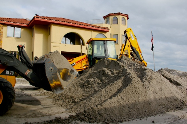<p>Crews with backhoes on South Iroquois Avenue in Margate scoop sand off the street and return it to the beach. (Emma Lee/for NewsWorks)</p>
