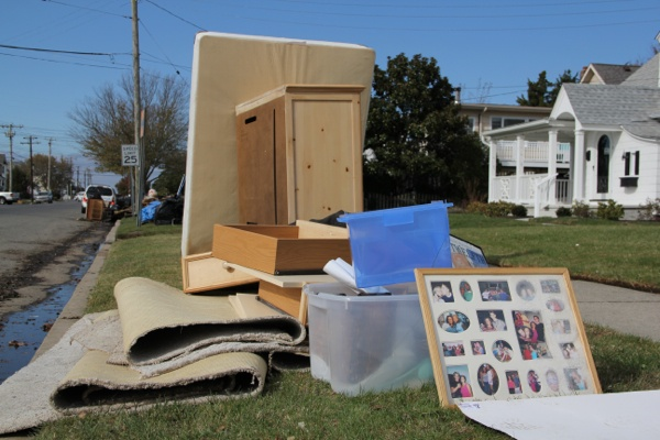 <p>On Battersea Avenue in Ocean City, water damaged belongings are piled by the curb for pickup. (Emma Lee/for NewsWorks)</p>