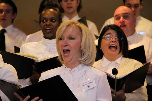 <p>Mariann Gilbride and a host of singers at St. Agnes Church in Blackwood make a joyful noice on the occasion of the installation of Bishop Dennis Sullivan as Bishop of Camden. (Emma Lee/for NewsWorks)</p>