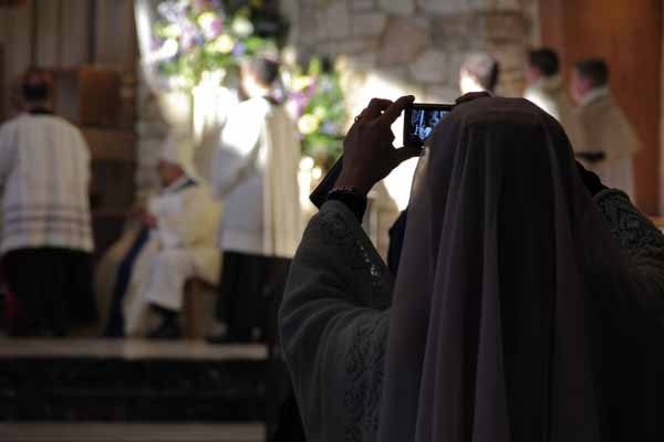 <p>A young woman uses her smartphone to record the installation of the 8th Bishop of Camden, Dennis J. Sullivan. (Emma Lee/for NewsWorks)</p>