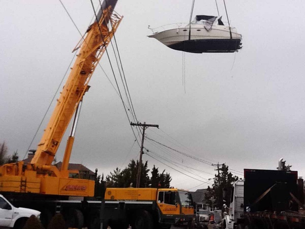 <p>A massive crane was used to lift boats over houses and power lines so the vessels could be transported to the mainland for winter storage. (Photo courtesy of Jimmy Ryan)</p>