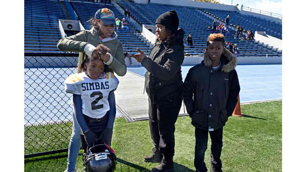During the last game of the season in Asbury Park, Jasmine Skinner braids Janiyah Hill's hair closer to her scalp so her helmet will fit better; at right is Hill's mother, Renekia Robinson and Hill's brother, Izayah Hil, 10.