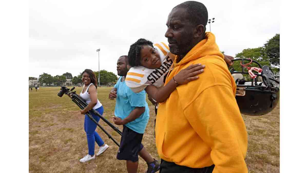 Simbas coach Orlando Council-Pettigrew carries Janiyah Hill off the field; at left is Hill's mother, Renekia Robinson; and in the middle is parent Christopher Johnson, whose son is also on the team.