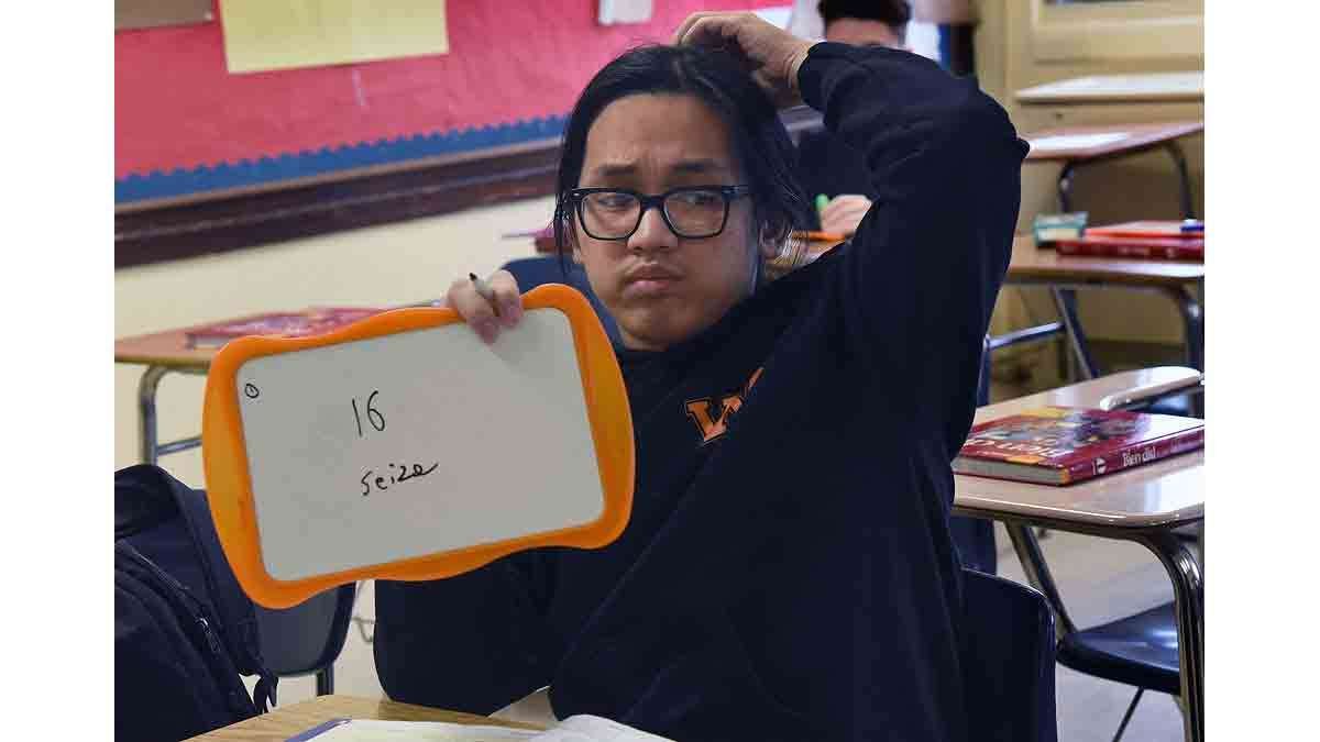 Minh Le, 16, holds up an answer in Saillard's French class during a lesson on numbers.