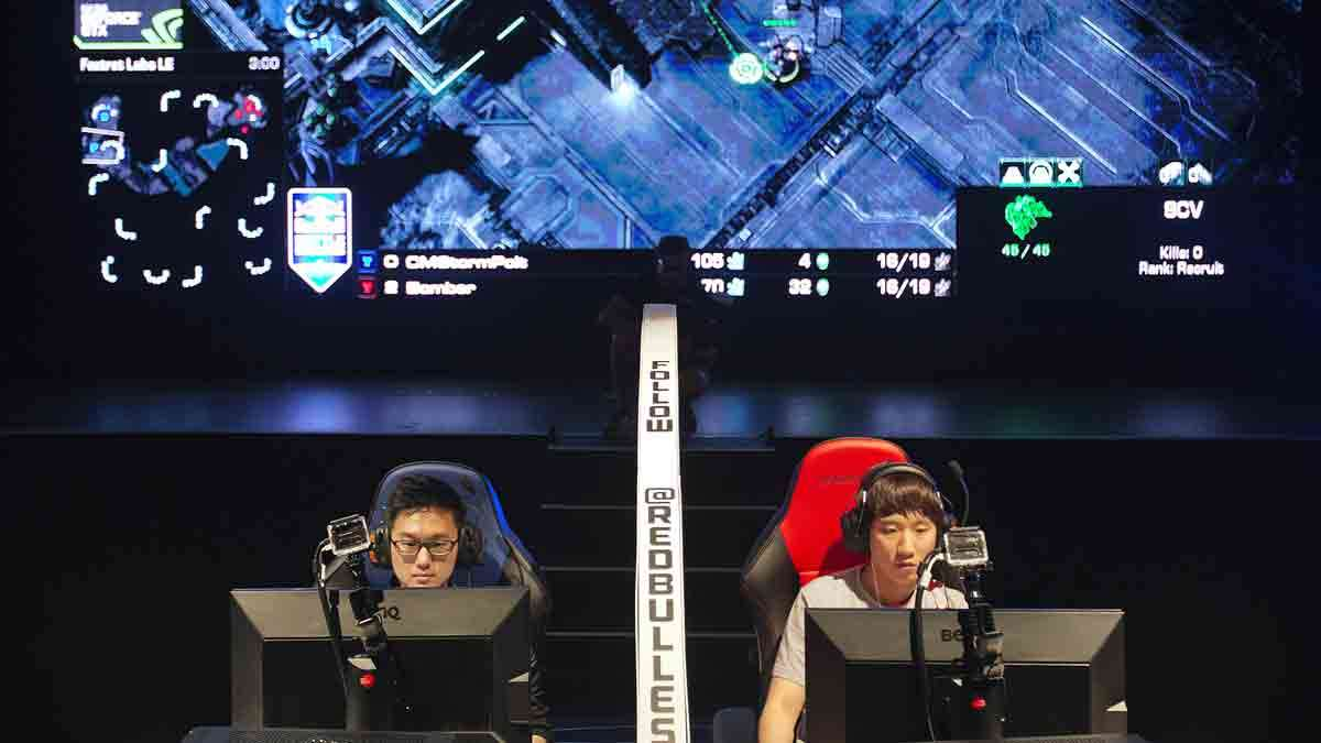 In this July 13, 2014 photo, Choi Seong Hun, (left), and Choi Ji Sung, both of South Korea, are separated by a divider as they compete against each other in the finals of the Red Bull Battle Grounds 'StarCraft II' video game tournament in Atlanta.