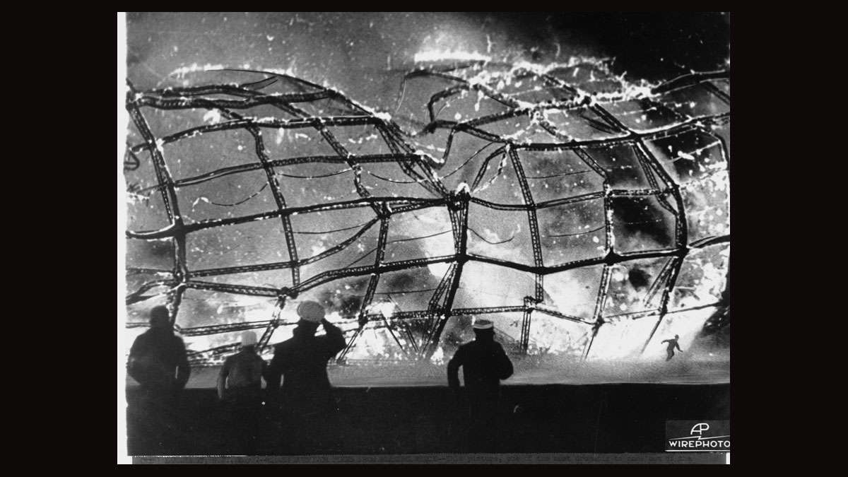 The burning Hindenburg is reduced to ruins as a survivor, lower right hand corner, runs to safety, May 6, 1937, after it exploded on mooring at Lakehurst Naval Air Station in New Jersey.