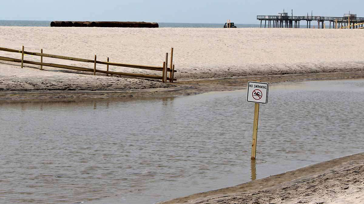 A no swimming sign sits in a pool of dirty water after this weekend's heavy rainfall.
