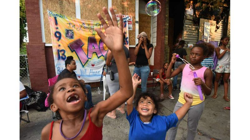On July 31, Zephaniah Williams, 6, plays with bubbles at the sidewalk memorial for her cousin, Laiyannie Williams. Next to her at right is Laiyannie's best friend, Aaliyah Roberts, 3.
