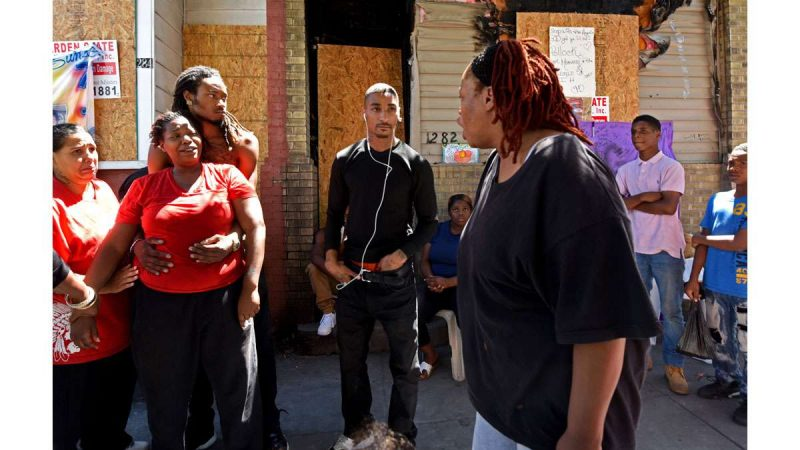 Outside the ravaged rowhouse on July 31, Elisha Williams, left--whose daughter, Laiyannie Williams, was killed in the blaze--talks to her mother, Victoria Williams, right.