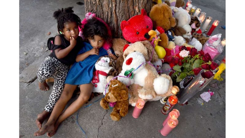 On July 31, Zariah Williams, 2; and Aaliyah Roberts, 3; cuddle up with the stuffed animals left in memoriam for Zariah's cousin, Laiyannie