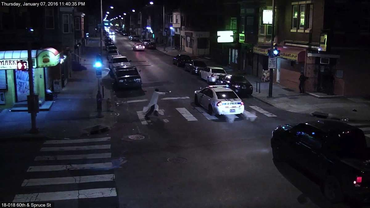 In stills from a surveillance video, a man is seen approaching Officer Jesse Hartnett, shooting into his patrol car and then running away. The wounded officer emerges from the car and pursues the suspect. (Photos provided by Philadelphia Police)
